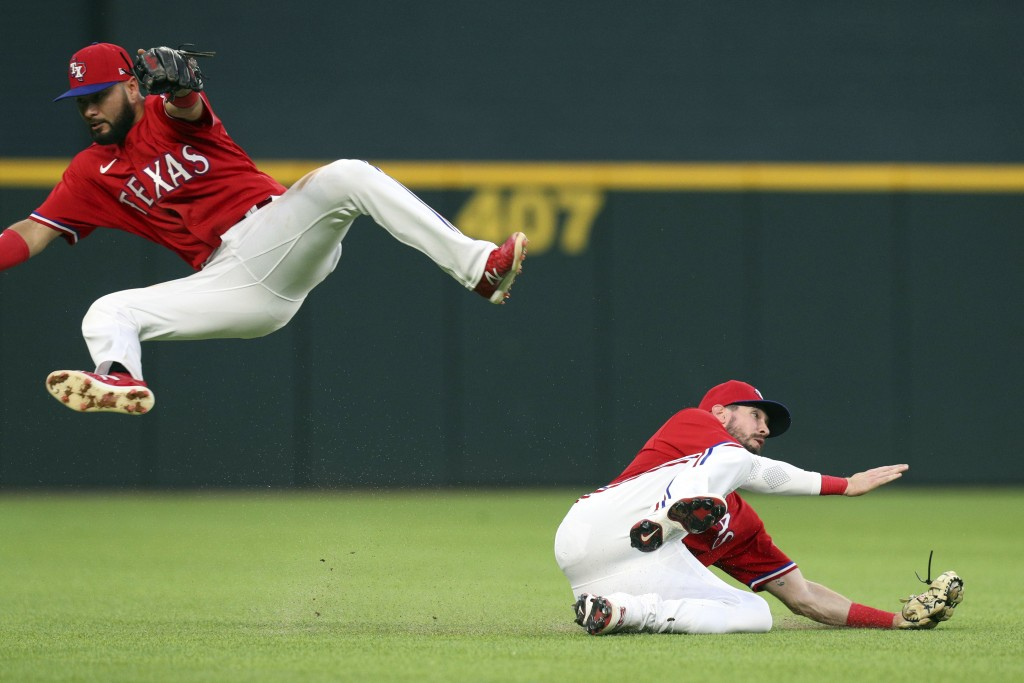 Texas Rangers shortstop Isiah Kiner-Falefa leaps to avoid left fielder David Dahl (21) as he catches a fly ball hit by Seattle Mariners' Kyle Seager d...