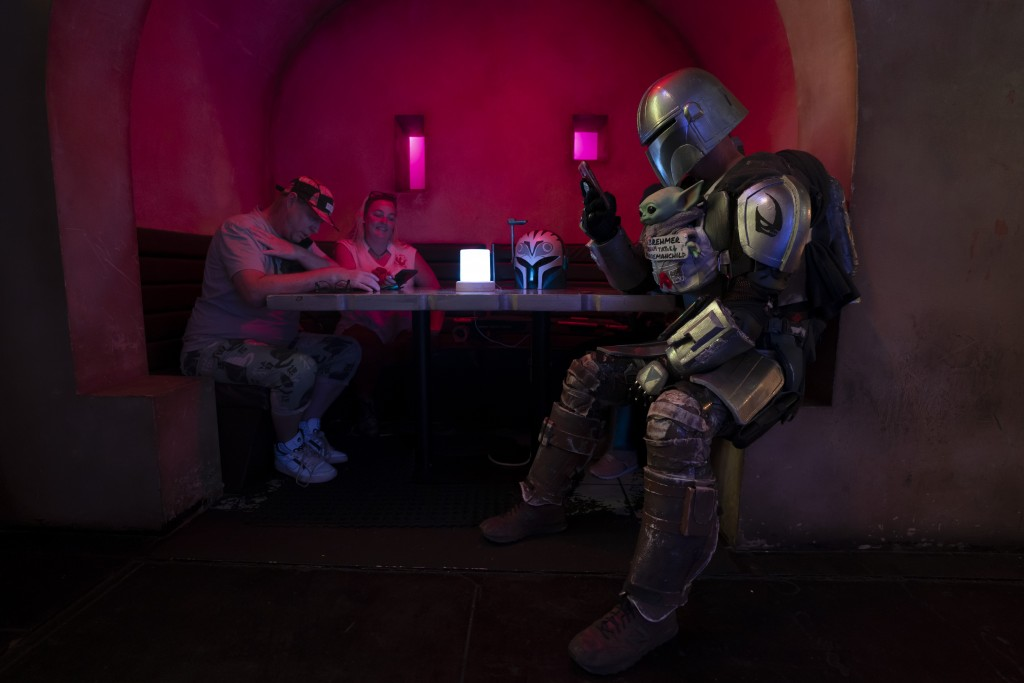 Dressed in a Star Wars costume, Tim Brehmer, right, sits in a booth as customers gather to celebrate the Star Wars Day at Scum and Villainy Cantina, a...