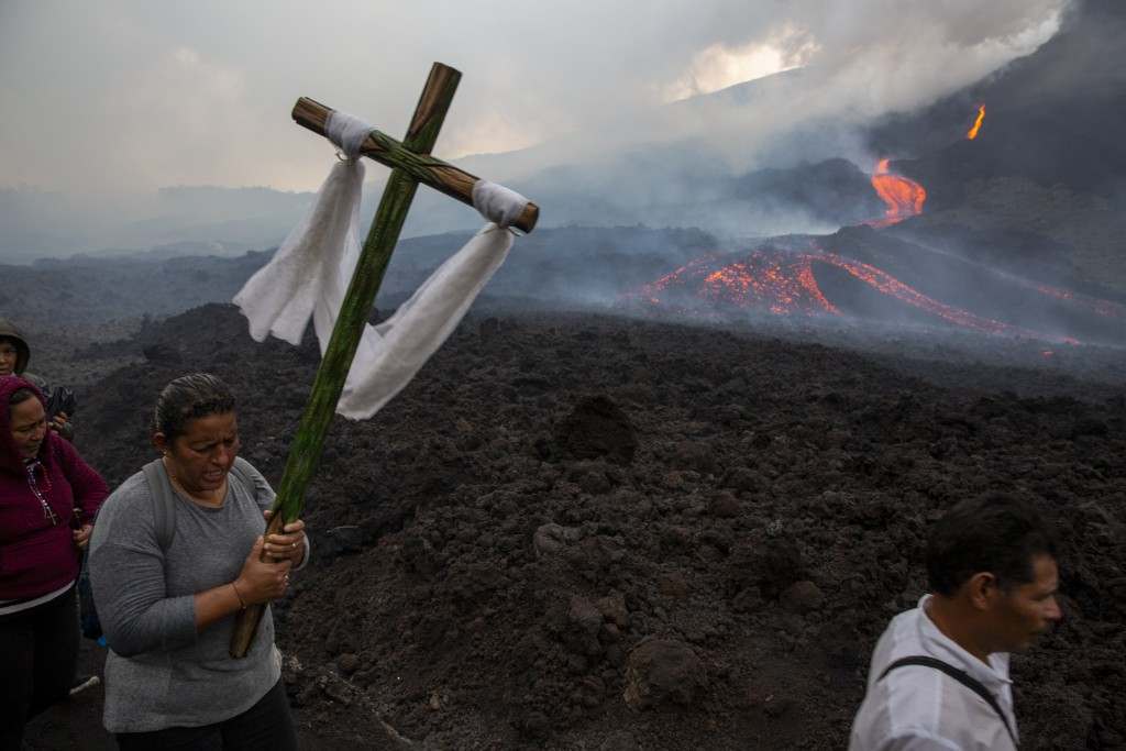 A woman carries a wooden cross during a pilgrimage to pray that the Pacaya volcano decreases its activity, in San Vicente Pacaya, Guatemala, Wednesday...