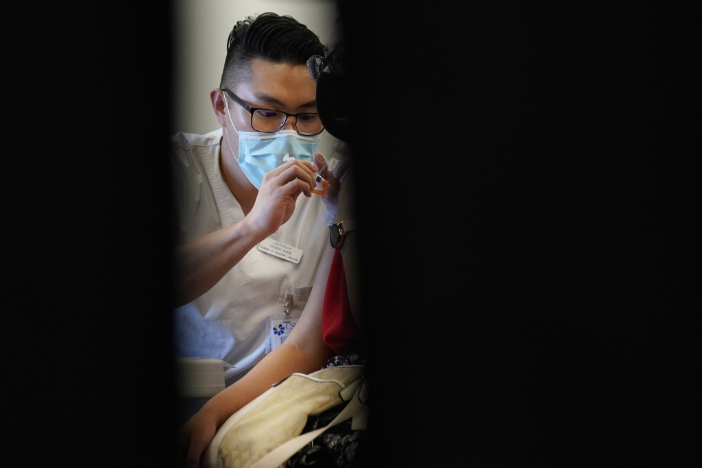 FILE - In this April 26, 2021, file photo, Johnson Shao, a nursing student at the College of Southern Nevada, administers the Moderna COVID-19 vaccine...