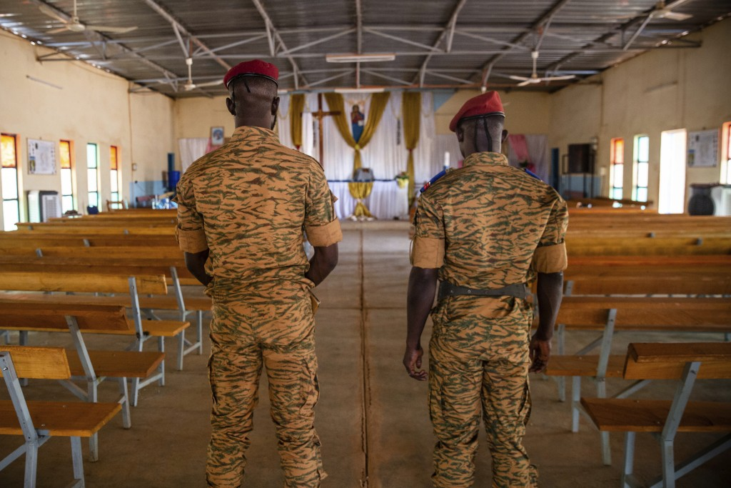Two soldiers stand in the Catholic church at the 10th RCAS army barracks in Kaya, Burkina Faso, Saturday, April 10, 2021. Once considered a beacon of ...