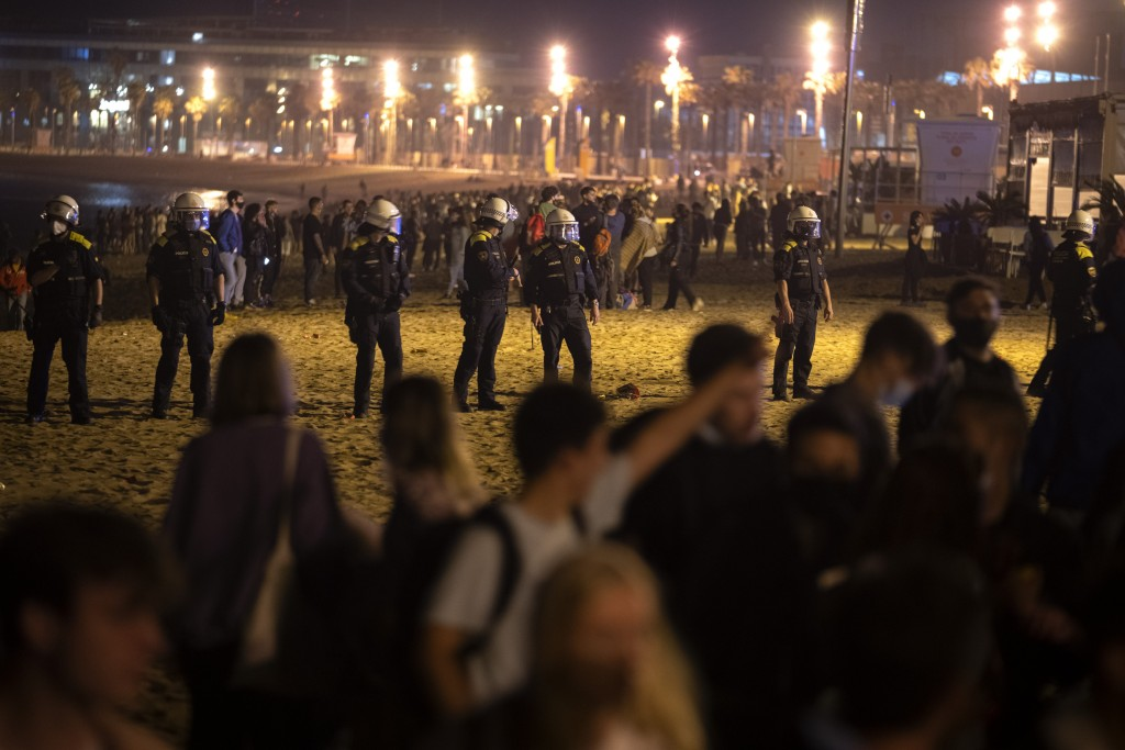 Police officers stand guard as people crowded on the beach in Barcelona, Spain, Sunday, May 9, 2021. Barcelona residents were euphoric as the clock st...
