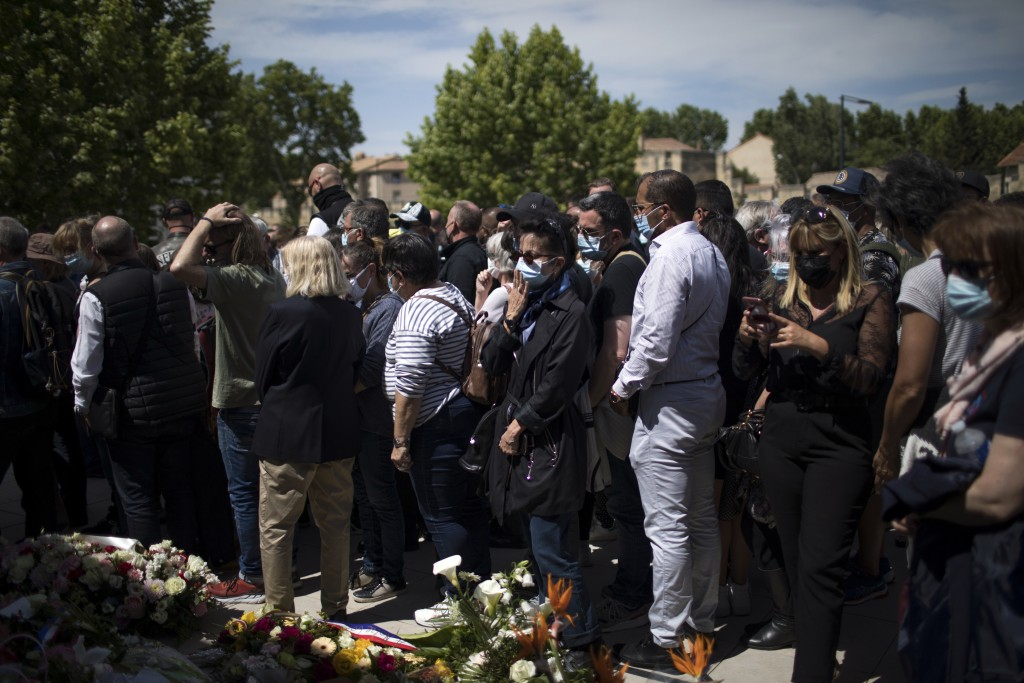 Police officers and civilians lay flowers at a police station in Avignon, southern France, Sunday, May 9, 2021. Police officers and civilians gathered...
