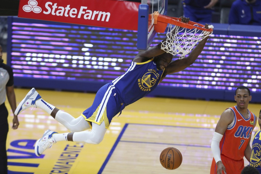 Golden State Warriors' Draymond Green hangs from the rim after scoring against Oklahoma City Thunder's Darius Bazley during the first half of an NBA b...