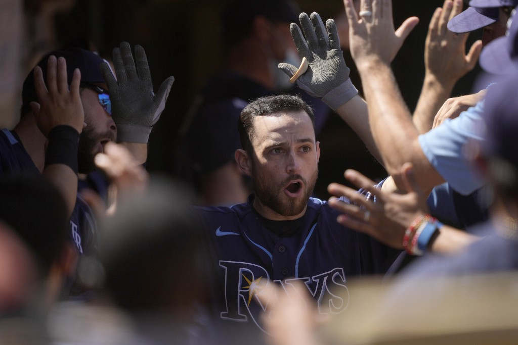 Tampa Bay Rays' Brandon Lowe, right, high-fives teammates as he reaches the dugout after hitting a two-run home run against the Oakland Athletics duri...