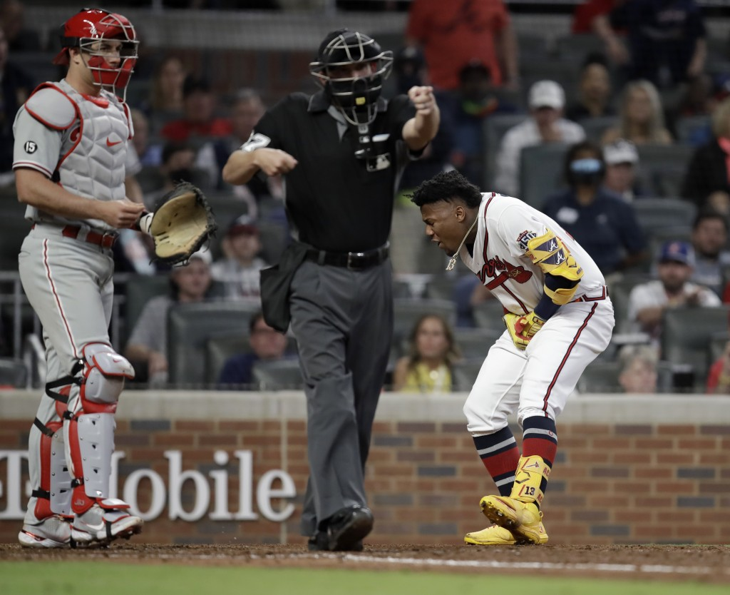 Atlanta Braves' Ronald Acuna Jr., right, reacts after being hit by a pitch thrown by Philadelphia Phillies' Sam Coonrod (not shown) in the seventh inn...