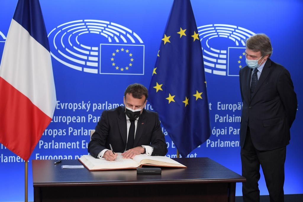 French President Emmanuel Macron signs a book next to European Parliament President David Sassoli before taking part in the Europe Day and the Confere...