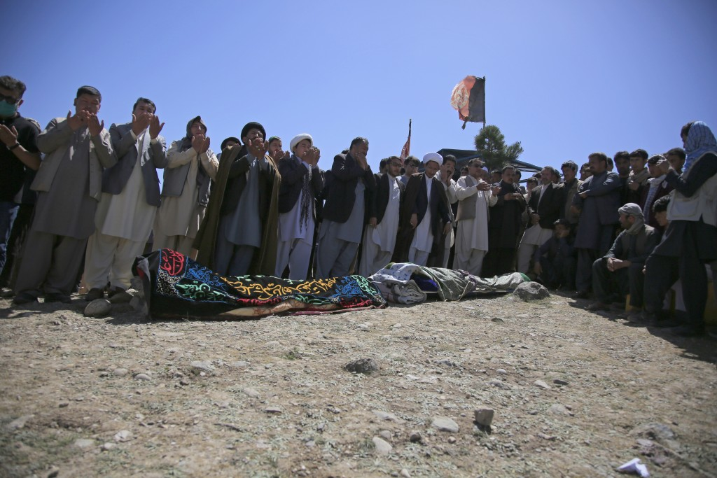 Afghans pray during the funeral of victims of deadly bombings on Saturday near a school, at a cemetery west of Kabul, Afghanistan, Sunday, May 9, 2021...