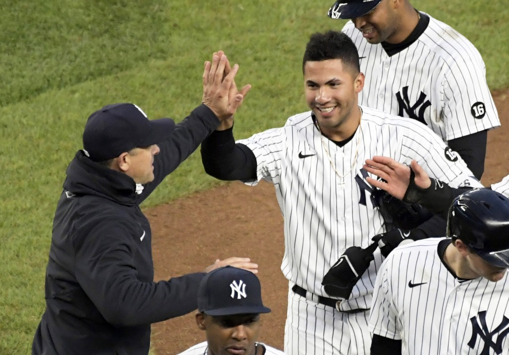 New York Yankees' Gleyber Torres is congratulated by manager Aaron Boone after Torres drove in the winning run in the 11th inning of the team's baseba...