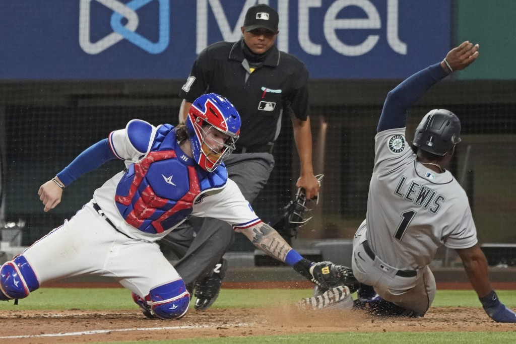 Seattle Mariners base runner Kyle Lewis is tagged out at home by Texas Rangers catcher Jonah Heim to end a baseball game in the ninth inning Saturday,...