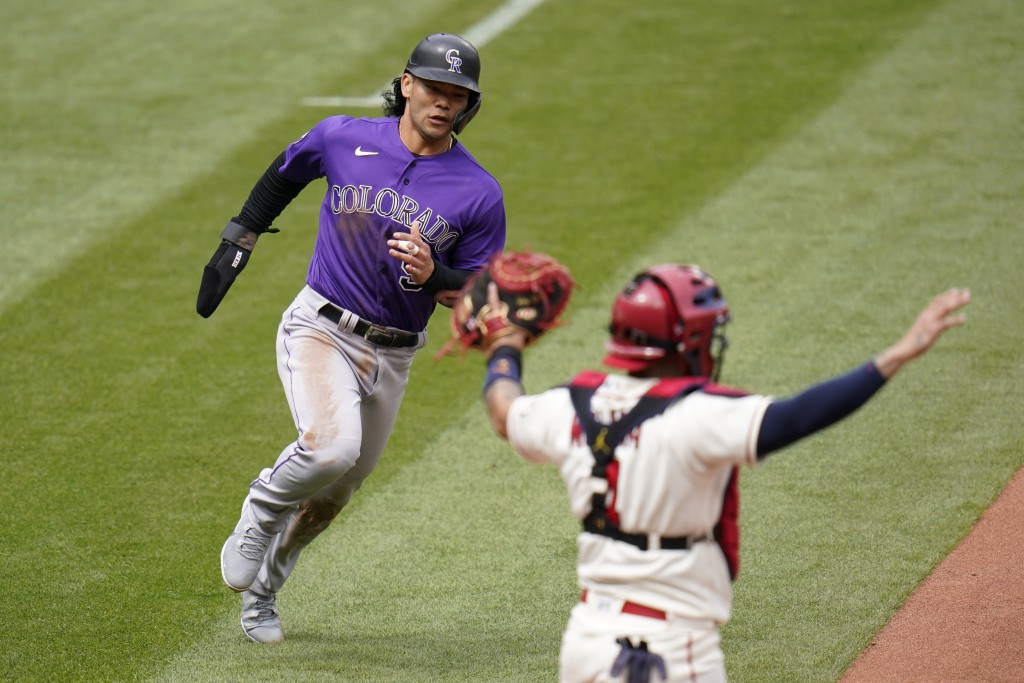 Colorado Rockies' Connor Joe, left, scores past St. Louis Cardinals catcher Yadier Molina on a three-run double by Dom Nunez during the fifth inning o...