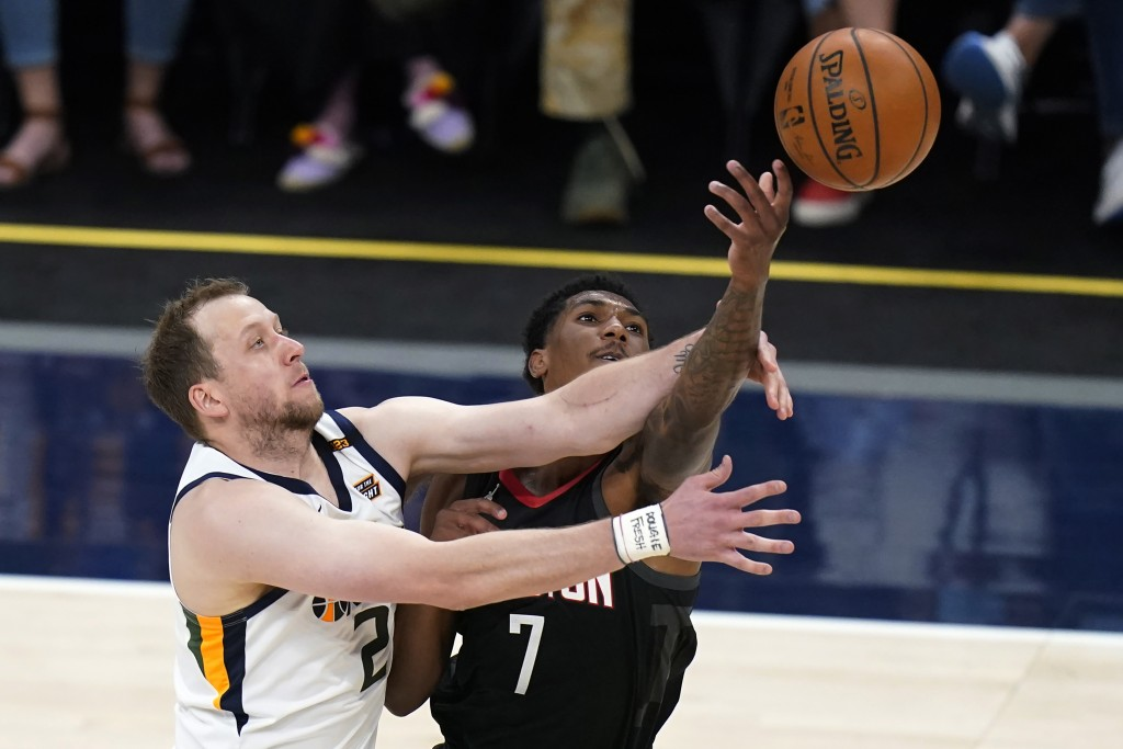 Utah Jazz guard Joe Ingles (2) and Houston Rockets guard Armoni Brooks (7) reach for the ball during the first half of an NBA basketball game Saturday...