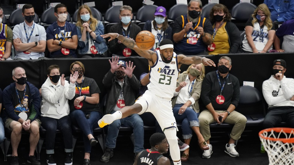 Utah Jazz forward Royce O'Neale (23) saves the ball as fans sitting courtside watch during the first half of the team's NBA basketball game against th...