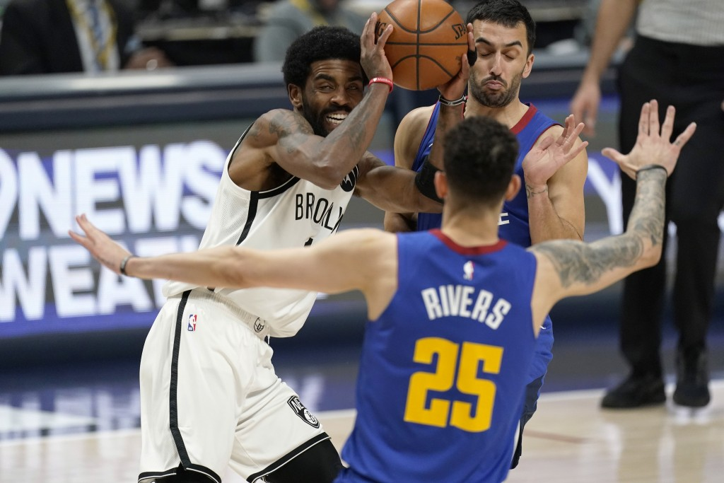 Brooklyn Nets guard Kyrie Irving is defended by Denver Nuggets guards Austin Rivers, front, and Facundo Campazzo during the second half of an NBA bask...