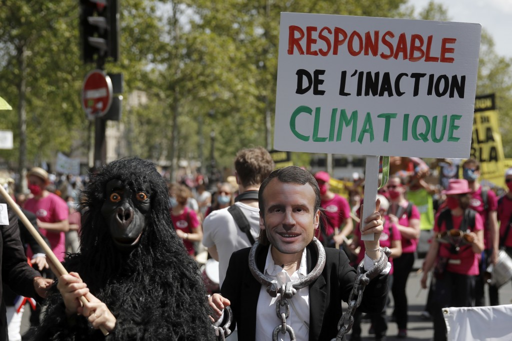A protester wearing a mask depicting French President Emmanuel Macron holds a bord reading «Liable for climate inaction» during a rally against the ...