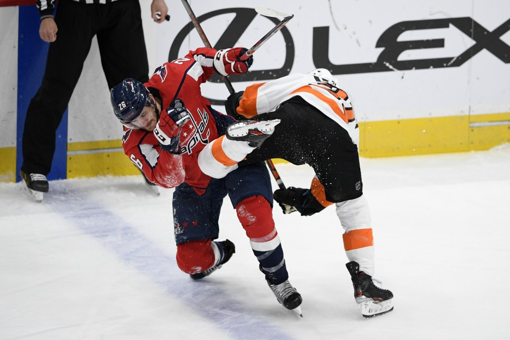Washington Capitals center Nic Dowd (26) and Philadelphia Flyers center Scott Laughton, right, collide during the first period of an NHL hockey game S...