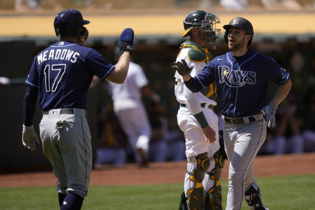 Tampa Bay Rays second baseman Brandon Lowe, right, high-fives teammate Austin Meadows (17) after hitting a two-run home run off Oakland Athletics star...