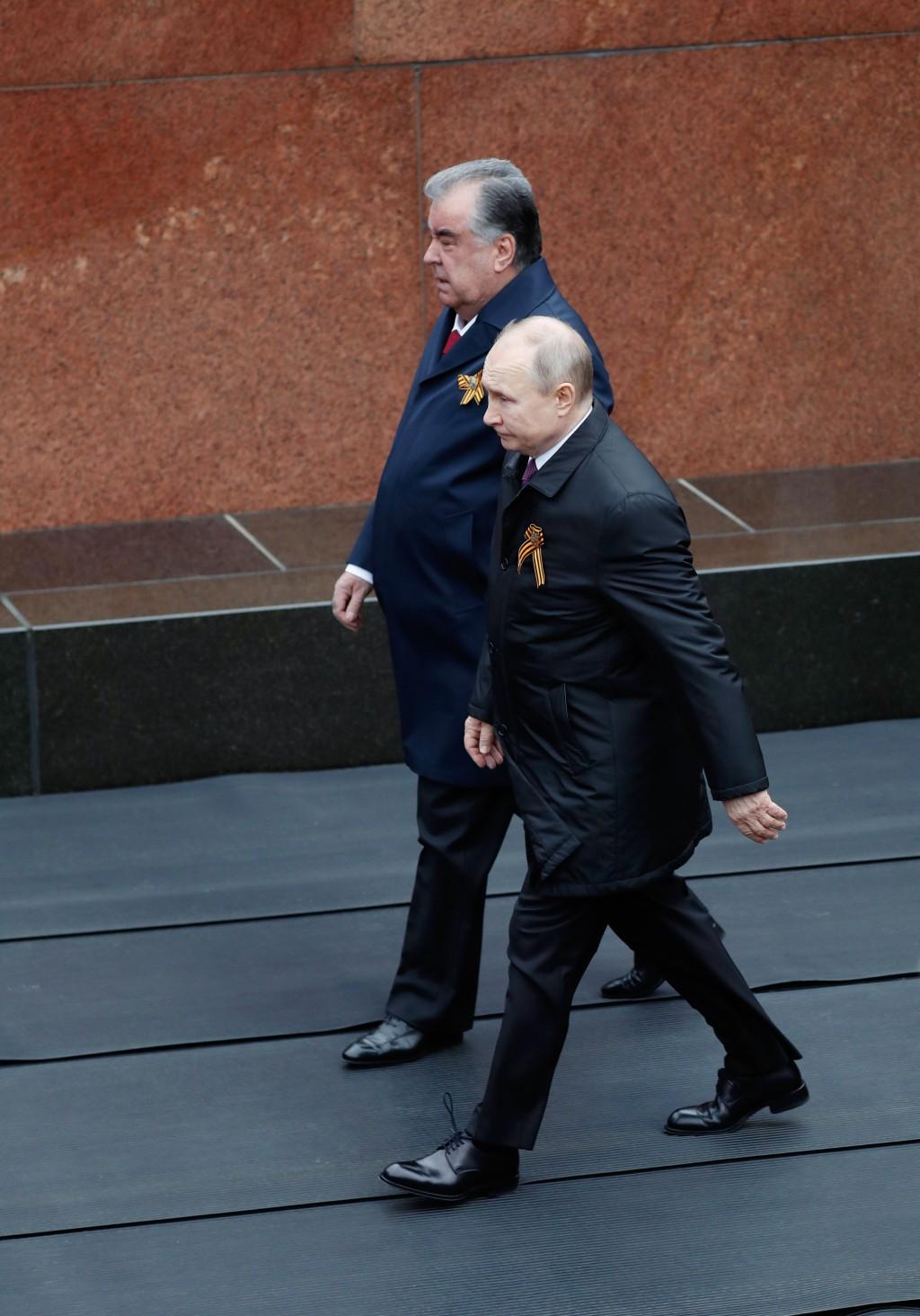 Russian President Vladimir Putin, right, and Tajikistan's President Emomali Rakhmon walk before the Victory Day military parade in Moscow, Russia, Sun...