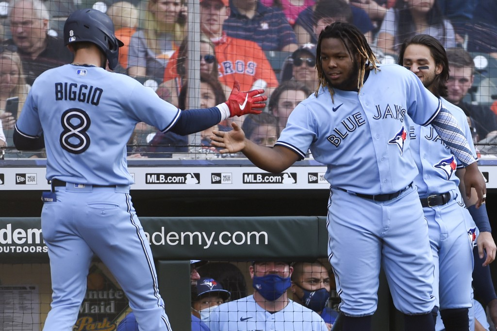 Toronto Blue Jays' Cavan Biggio (8) celebrates with Vladimir Guerrero Jr. as Biggo returns to the dugout after hitting a two-run home run during the s...