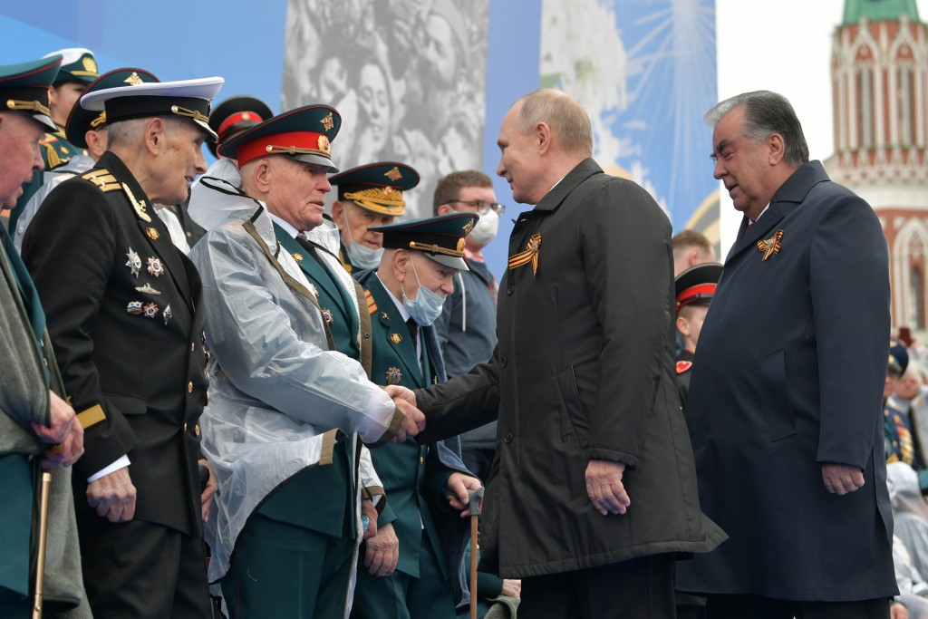 Russian President Vladimir Putin, second from right, and Tajikistan's President Emomali Rakhmon, right, shake hands with WWII veterans before the Vict...