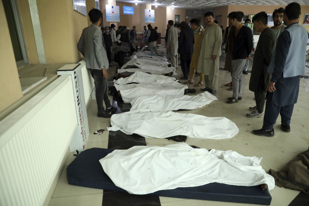 Afghan men try to identify the dead bodies at a hospital after a bomb explosion near a school west of Kabul, Afghanistan, Saturday, May 8, 2021. A bom...