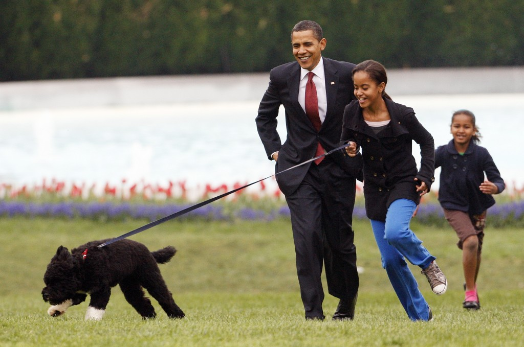 FILE - Int his April 14, 2009, file photo Malia Obama runs with Bo, followed by President Barack Obama and Sasha Obama, on the South Lawn of the White...