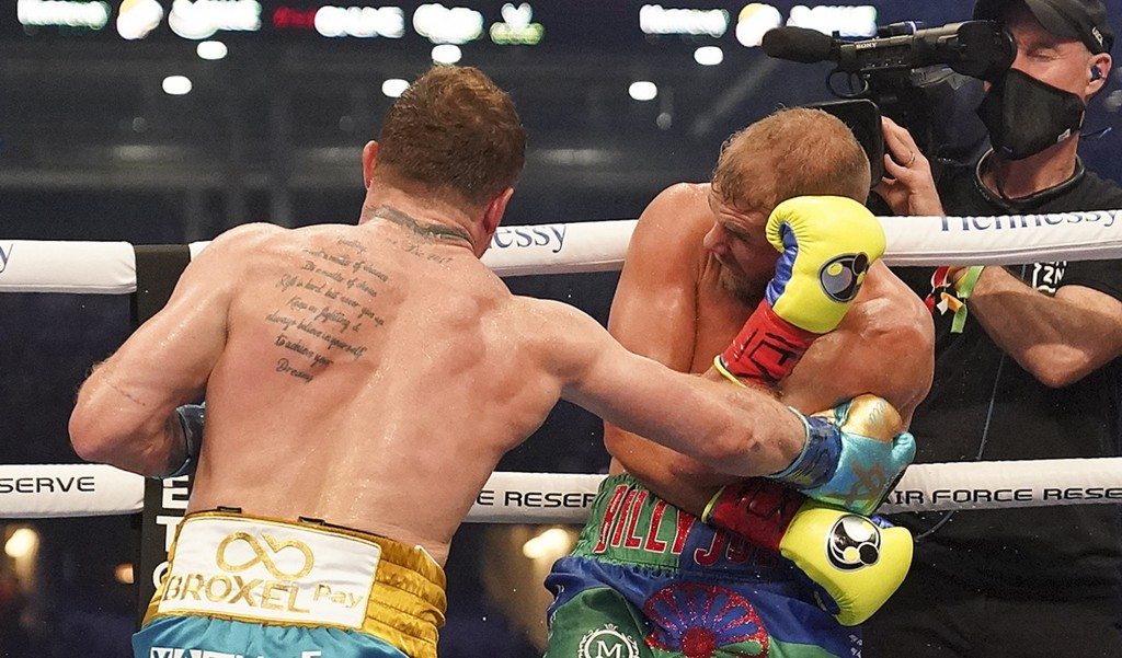 Canelo Alvarez, left, throws a punch against Billy Joe Saunders during a unified super middleweight world championship boxing match, Saturday, May 8, ...
