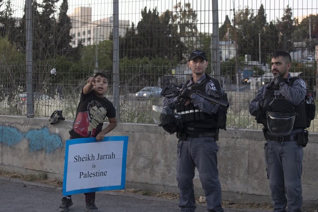 A Palestinian boy speaks to police during a protest against the forcible eviction of Palestinians from their homes in the Sheikh Jarrah neighborhood o...