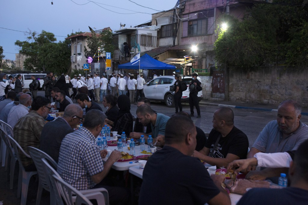 Israeli police stand guard as Palestinian Muslims break their fast during the holy month of Ramadan and Jewish settlers gather to begin Shabbat at a P...