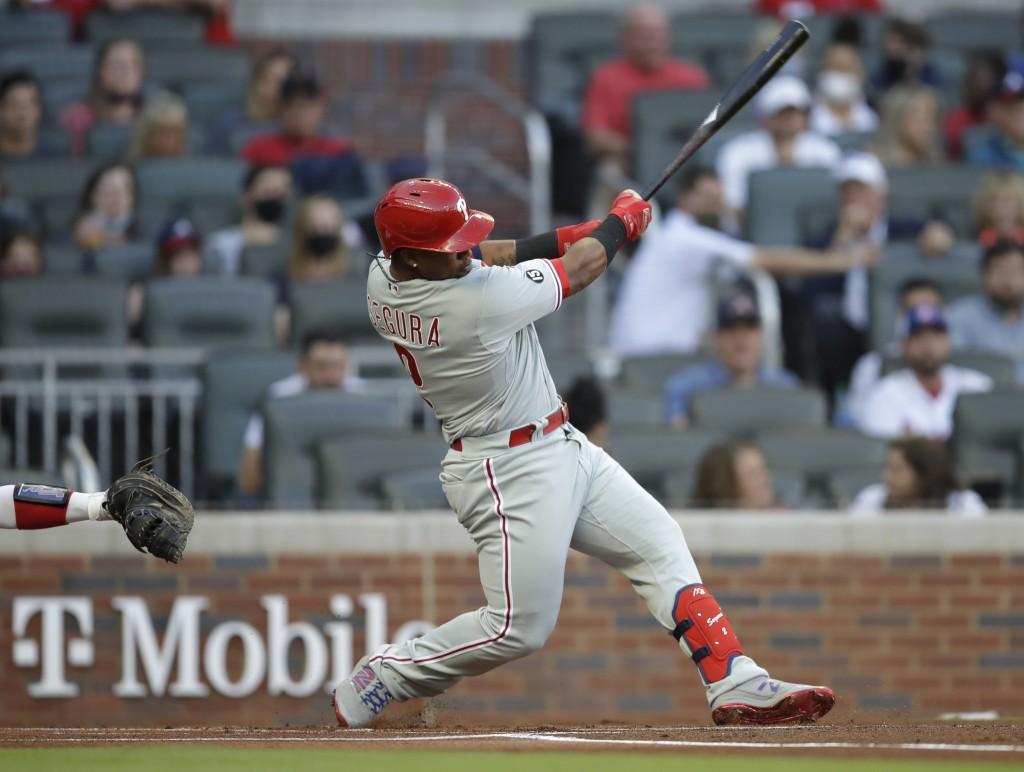 Philadelphia Phillies' Jean Segura swings for a home run off Atlanta Braves pitcher Ian Anderson in the first inning of a baseball game Saturday, May ...