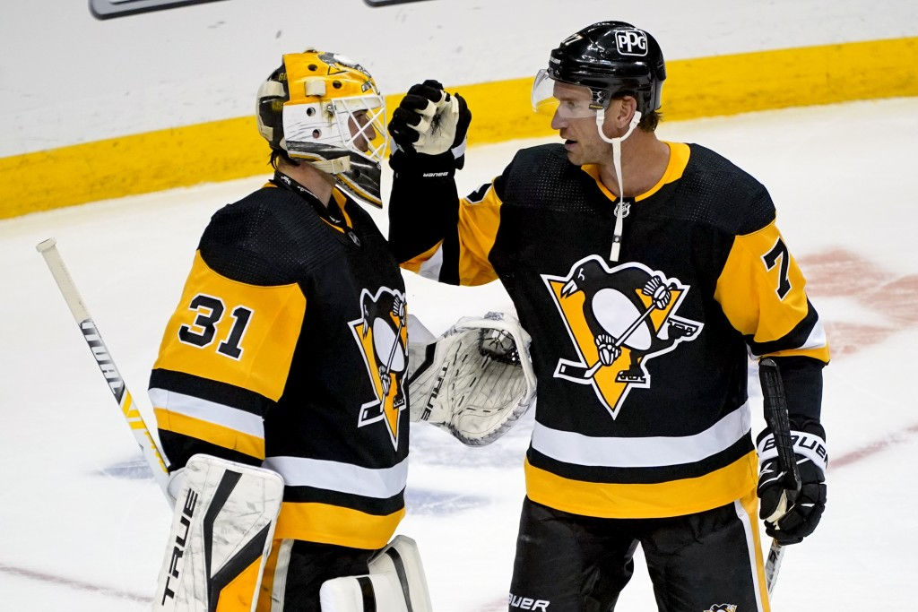 Pittsburgh Penguins goaltender Maxime Lagace (31) celebrates his first career shutout with Jeff Carter after an NHL hockey game against the Buffalo Sa...