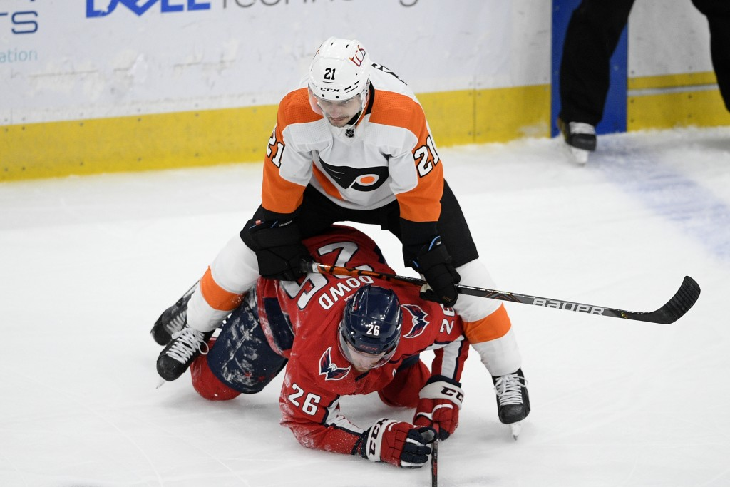 Philadelphia Flyers center Scott Laughton (21) stands over Washington Capitals center Nic Dowd (26) during the first period of an NHL hockey game Satu...