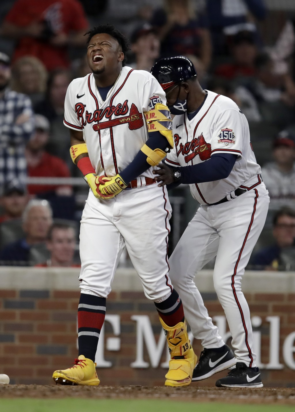 Atlanta Braves' Ronald Acuna Jr., left, is assisted by third base coach Ron Washington after being hit by a pitch thrown by Philadelphia Phillies' Sam...