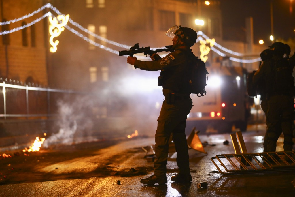 An Israeli police officer aims his rifle towards Palestinian demonstrators during clashes at Damascus Gate just outside Jerusalem's Old City, Saturday...