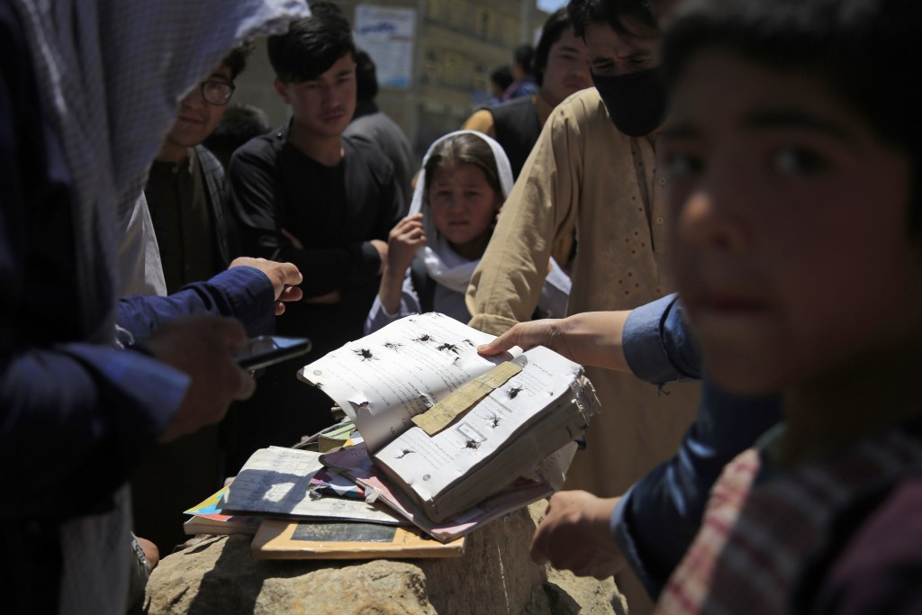 Afghans go through belongings left behind after deadly bombings on Saturday near a school in Kabul, Afghanistan, Sunday, May 9, 2021. The Interior Min...