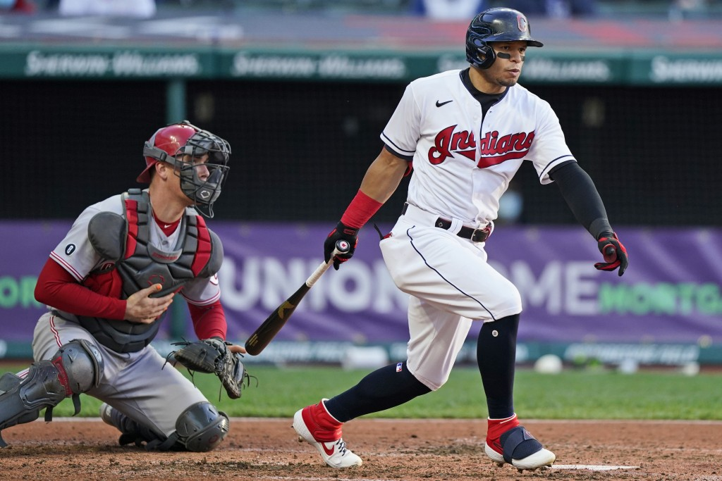 Cleveland Indians' Cesar Hernandez watches his three-run triple next to Cincinnati Reds catcher Tyler Stephenson the fourth inning of a baseball game ...