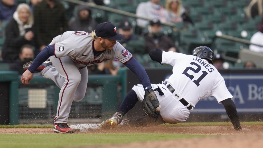 Detroit Tigers left fielder JaCoby Jones (21) slides safely into third base under the tag of Minnesota Twins third baseman Josh Donaldson (20) in the ...