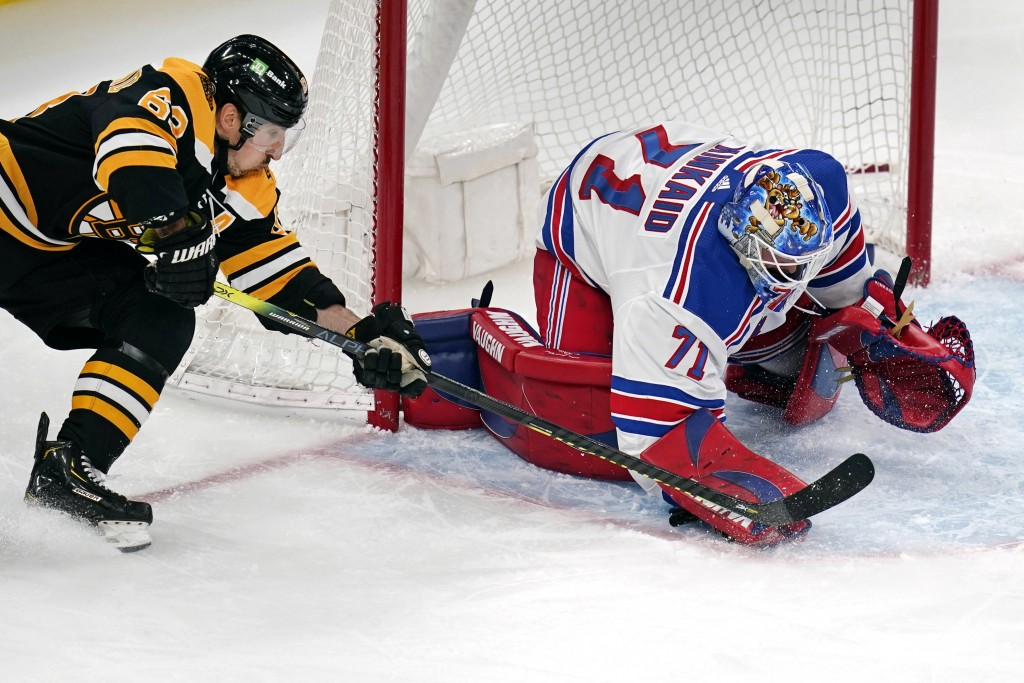 New York Rangers goaltender Keith Kinkaid (71) pounces on the puck as he makes a save against Boston Bruins center Brad Marchand (63) without his stic...