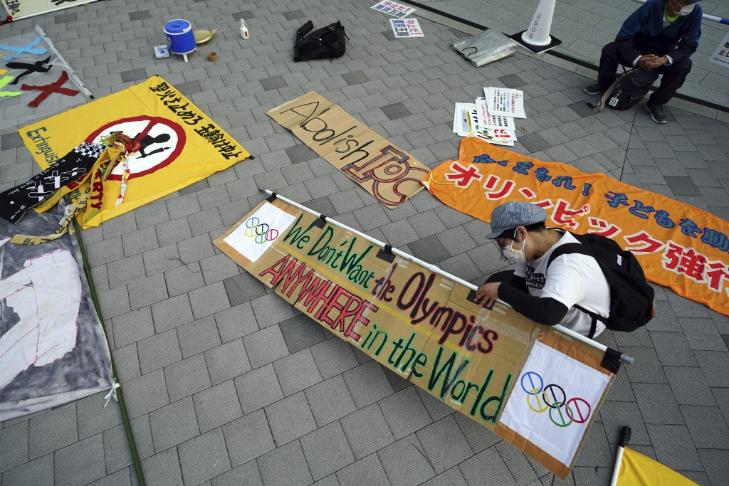 A participant against the Tokyo 2020 Olympics set to open in July, prepares banners to protest around Tokyo's National Stadium during an anti-Olympics...