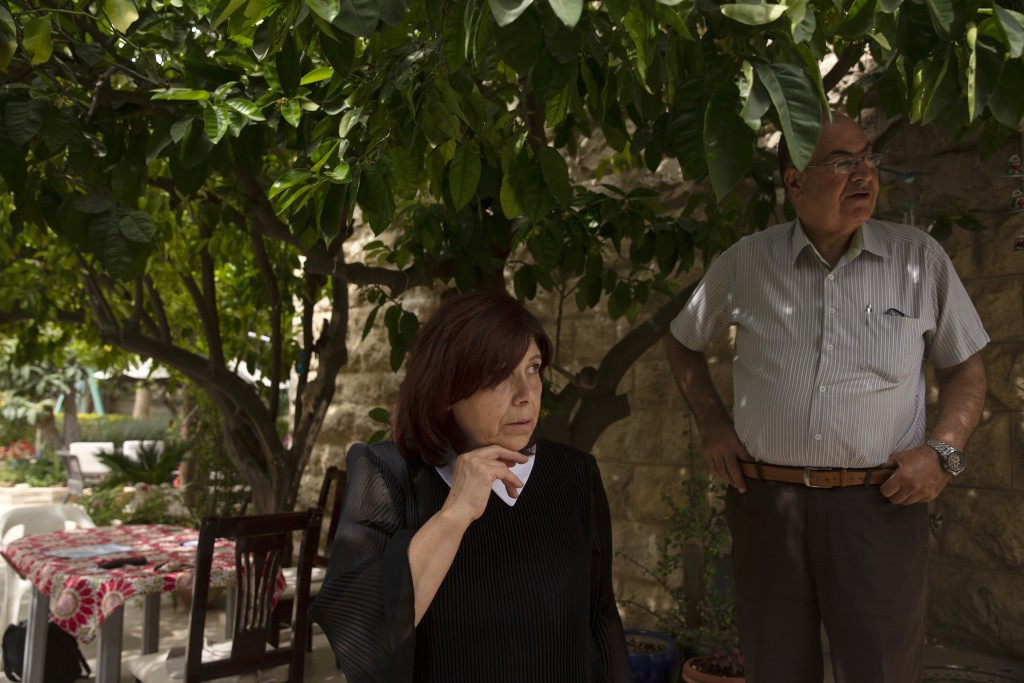 Samira Dajani and her husband, Adel Budeiri, stand in the shade of a tree in the garden of their home, where she has lived since childhood, in the She...