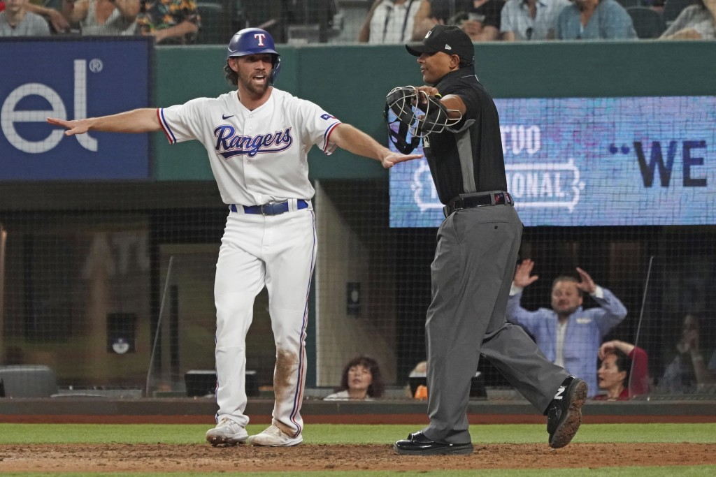 Texas Rangers base runner Charlie Culberson signals himself safe at home as he scores a run against the Seattle Mariners in the eighth inning of a bas...
