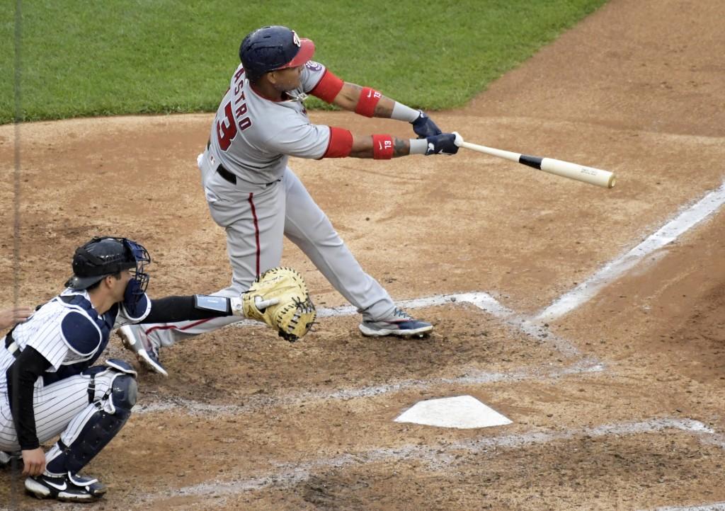 Washington Nationals' Starlin Castro (13) hits an RBI-single as New York Yankees catcher Kyle Higashioka (66) looks on during the sixth inning of a ba...