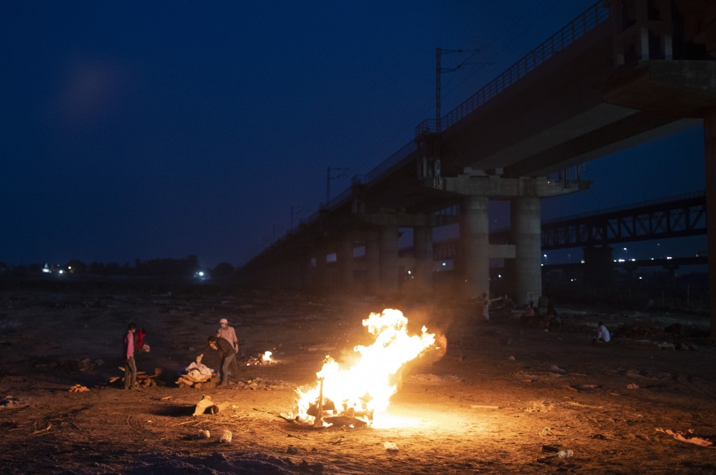Relatives stand near the funeral pyre of their loved one who died due to COVID-19 at a cremation ground in Prayagraj, India, Saturday, May 8, 2021. (A...