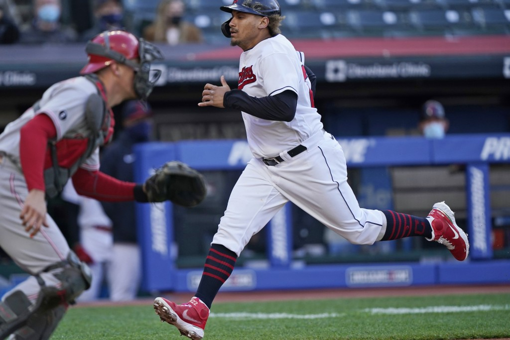 Cleveland Indians' Josh Naylor, right, scores as Cincinnati Reds catcher Tyler Stephenson waits for the throw during the second inning of a baseball g...