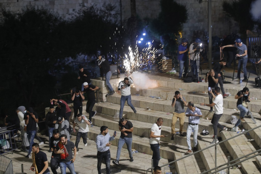 Palestinians run from stun grenades fired by Israeli police officers during clashes at Damascus Gate just outside Jerusalem's Old City, Saturday, May ...