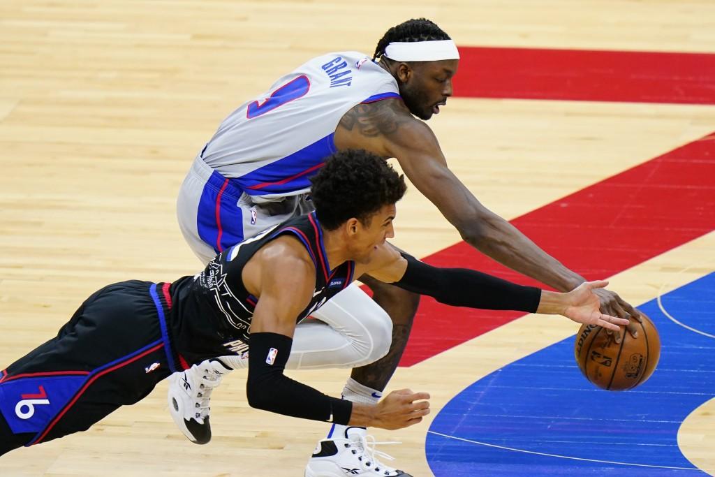 Philadelphia 76ers' Matisse Thybulle, left, dives for the ball against Detroit Pistons' Jerami Grant during the second half of an NBA basketball game,...