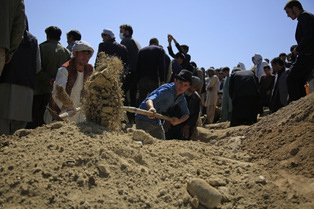 Afghan men bury a victim of deadly bombings on Saturday near a school, at a cemetery west of Kabul, Afghanistan, Sunday, May 9, 2021. The Interior Min...