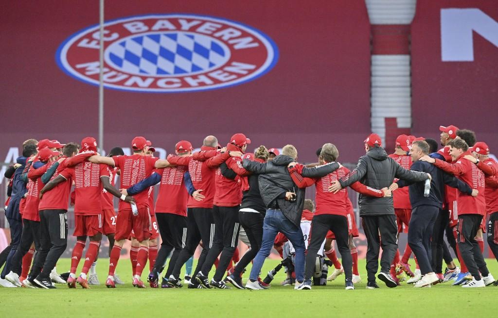 Bayern Munich's players and team members celebrate after they won the German Bundesliga soccer match between Bayern Munich and Borussia Moenchengladba...