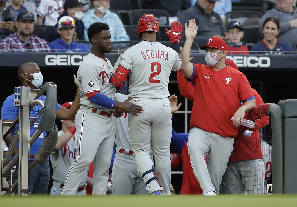 Philadelphia Phillies' Jean Segura (2) is congratulated upon his return to the dugout after hitting a home run off Atlanta Braves pitcher Ian Anderson...