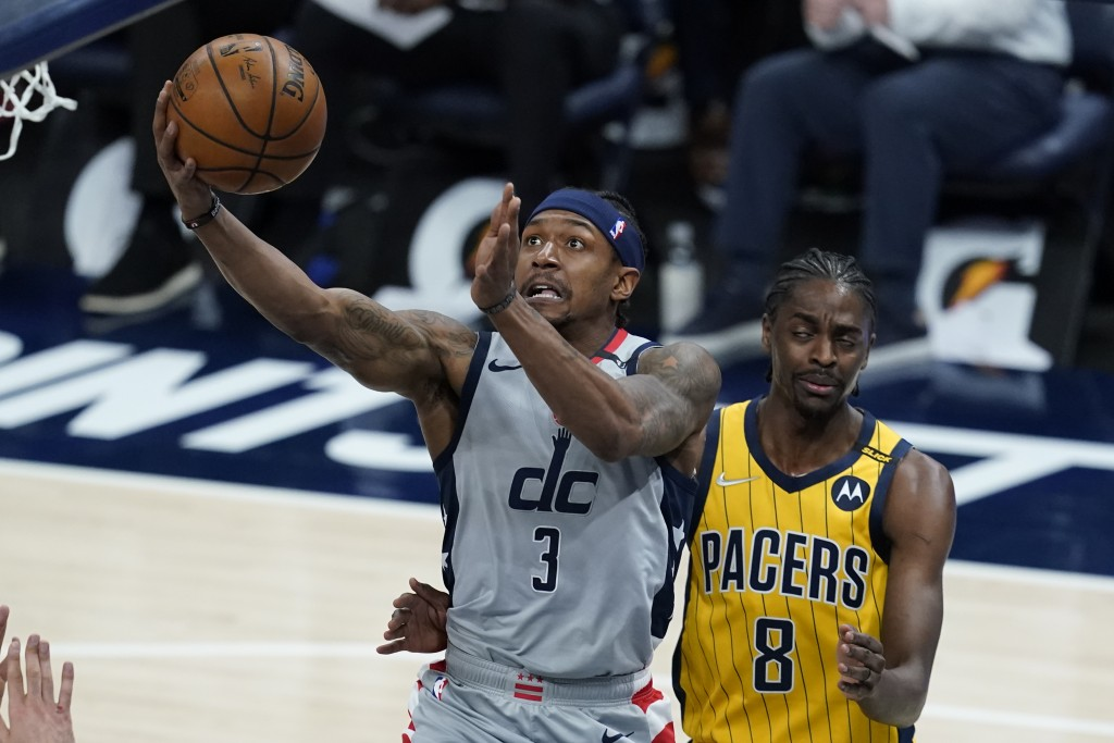 Washington Wizards' Bradley Beal (3) is fouled by Indiana Pacers' Justin Holiday (8) as he goes up for a shot during the first half of an NBA basketba...